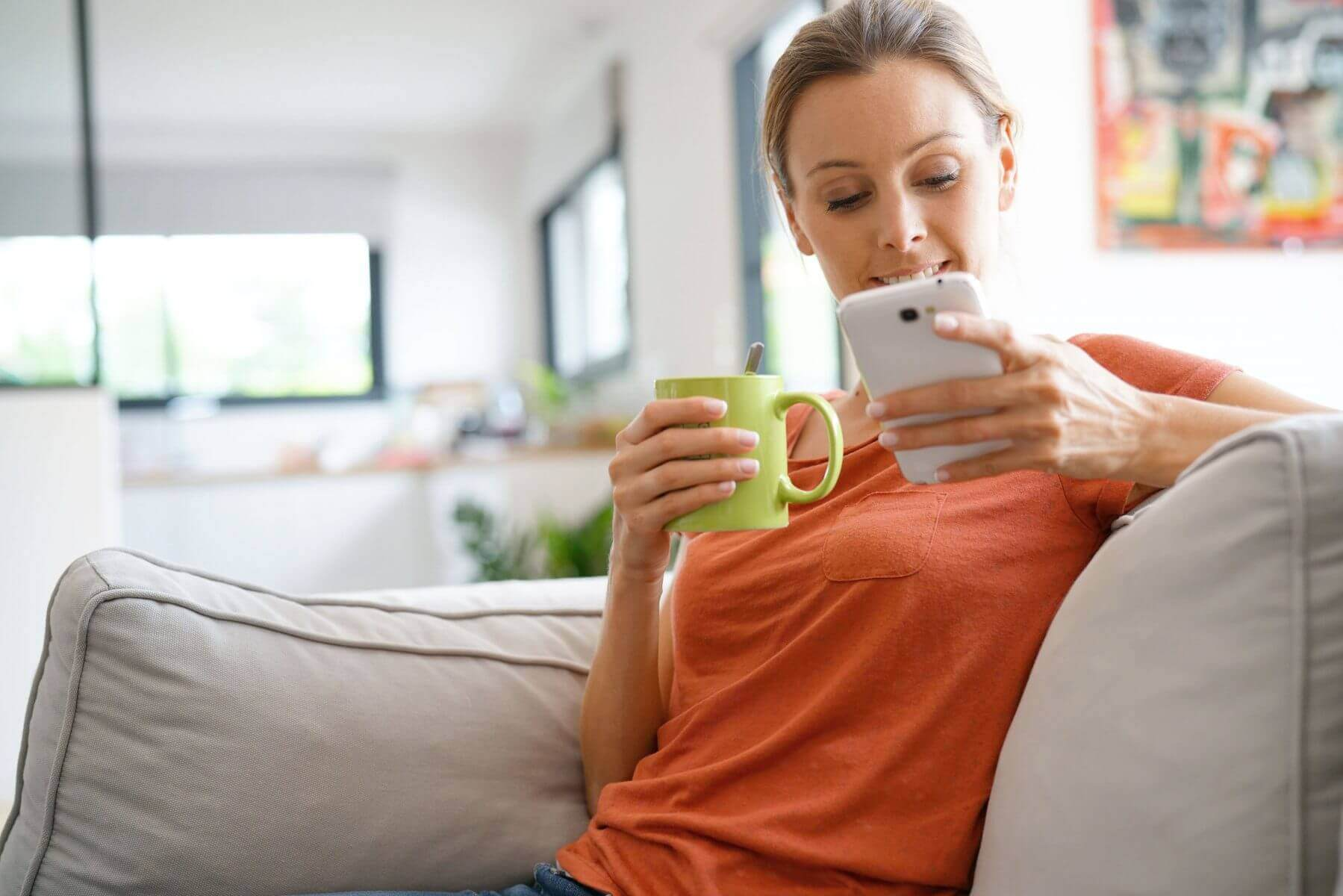 Woman drinking tea on the sofa with a phone
